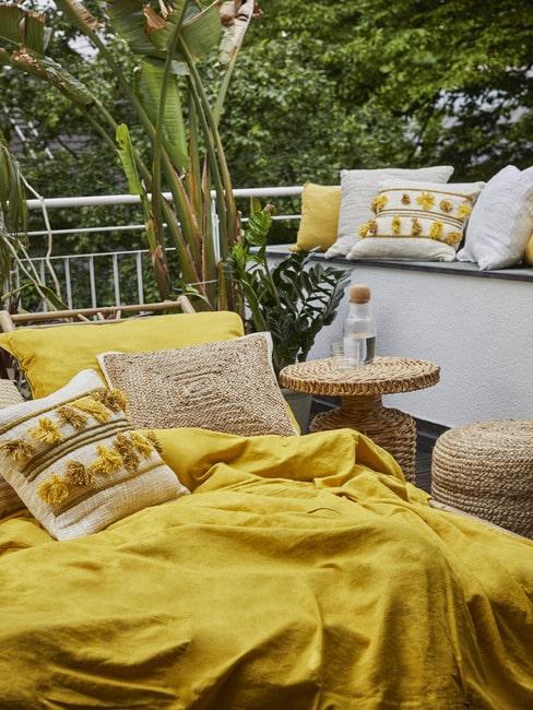 Taras z leżakim oraz rattanowym stoliczkiem oraz żółtymi tekstyliami