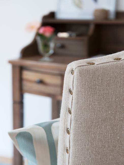 Fragment wnętrza w stylu rustykalnym, z drewnianym sekretarzykiem o fragmentem szarego, obitego krzesła