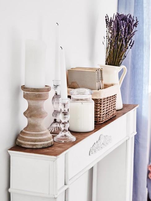 Biała półka w kształcie kominka z świecznikami, świecami oraz białym, ceramicznym wazonem z lawendą
