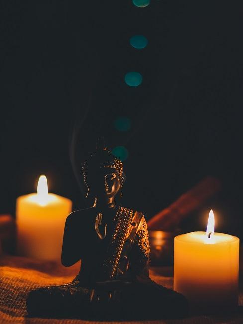 Mała figurka Buddy w ciemnym pokoju, za nią dwie płonące świece