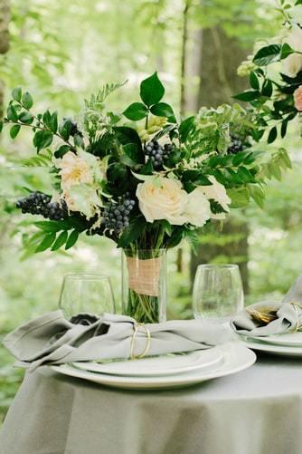 Biało-zielona aranżacja kwiatowa na stole weselnym