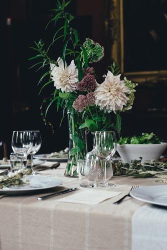 Stół weselny w stylu eleganckim w kwiatami w wazonie