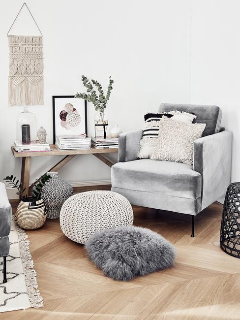 Fragment salonu w stylu boho z szarym fotelem, poduszkami oraz pufem