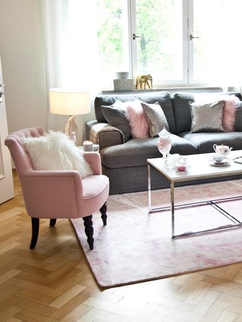 Jasny salon w stylu shabby chic z szarą kanapą, różowym fotelem oraz białym stolikiem kawowym