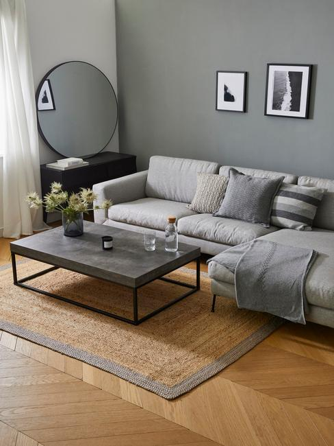 Szary salon z czarnym stolikiem kawowym, plecionym dywanem oraz lustrem na ścianie