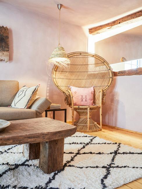 Jasny salon w stylu rustykalnym z drewnianym stolikiem kawowym, beżową kanapą oraz fotelem wykonanym z drewna bambusowego
