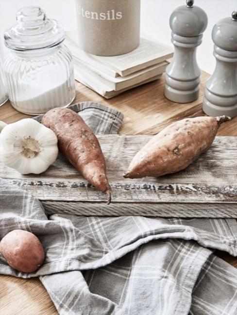 Küche im cleanen Landhausstil mit massivem Holzschneidebrett und Kartoffeln