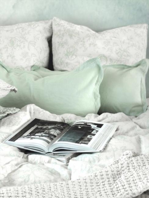 Cama en tonos verde pastel con una revista de decoración