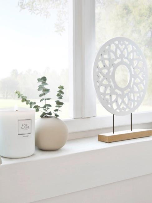 una ventana decorada con un jarrón pequeño, una figura decorativa y una vela blanca