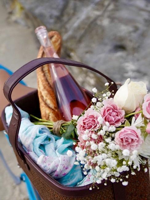 Bicyclette en gros plan avec panier rempli des fleurs et d'une bouteille