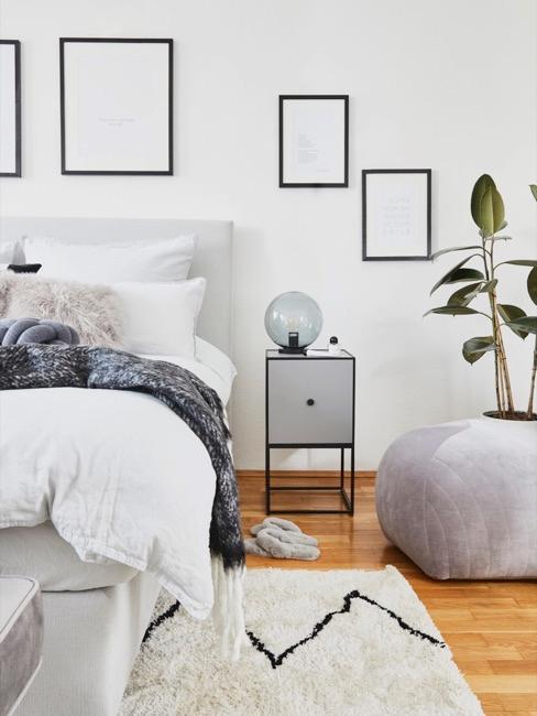 Sypialnia w naturalnym koloar oraz czarne ramki wiszące na ścianie
