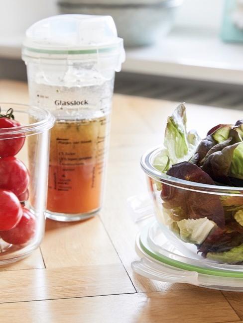 Sałata oraz pomidory umieszczona w plastikowym pudełku na stole,