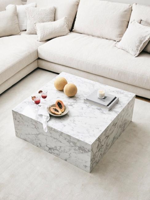 Jasny salon z kremową, narożną kanapą oraz designerskim, marmurowym stolikiem kawowym