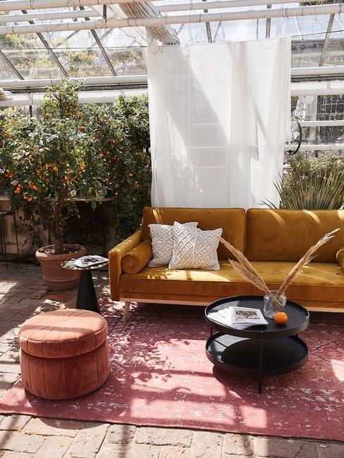 Divano giallo con cuscini bianchi, tavolino nero e pouff in giardino d'inverno