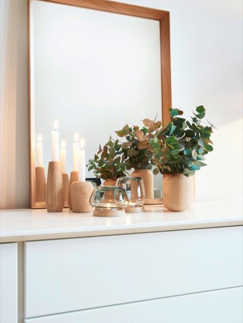 Komoda z drewnianymi wazonami i lustrem w drewnianej ramie