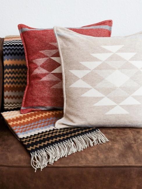 Skórzana kanapa w kolorze brązowym z poduszkami dekoracyjnymi i kocem.