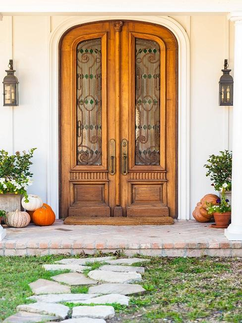 Große Haustüre aus Holz von außen, daneben Pflanzendeko