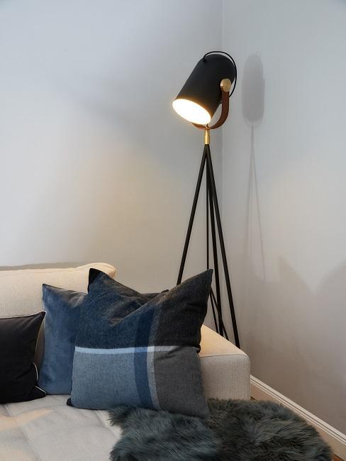 Czarna lampa stojąca obok sofy w salonie