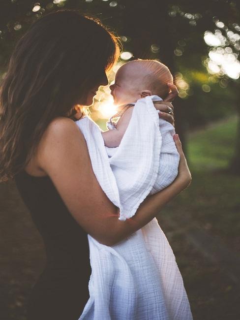 Mutter mit Ihrem Baby in ein Tuch eingewickelt auf dem Arm in der Natur