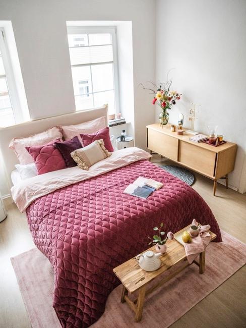 Dormitorio con colcha roja y con un banco pie de cama con un desauyono