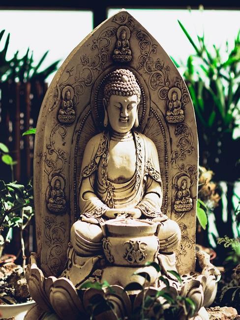 Große Buddha Figur aus Stein in der Mitte von vielen Pflanzen