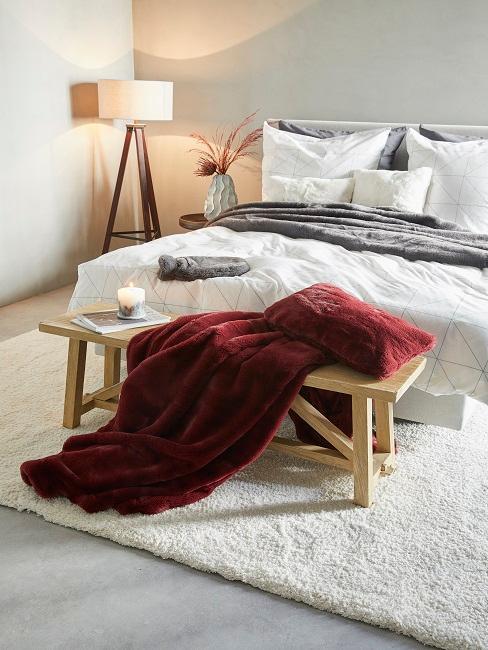 Mobili in camera con letto bianco, panchetta in legno e coperta rossa