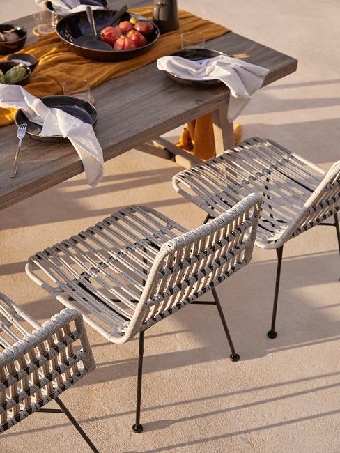 Stühle aus Rattan an einem großen Holztisch, der gedeckt ist