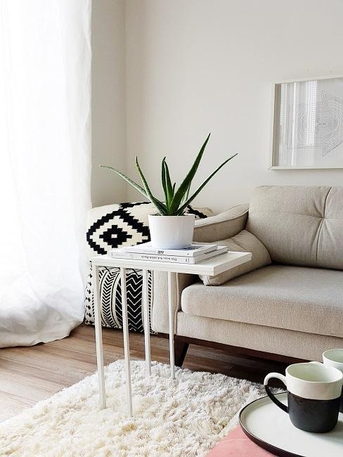 Helles Sofa neben zwei Ethno Kissen hinter einem Flausch-Teppich mit einem kleinen weißen Couchtisch