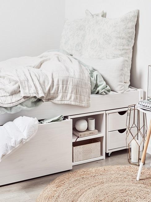 Ein weißes Holzbett mit mehreren Holzkästen teht im Schlafzimmer mit weißer Bettäsche.