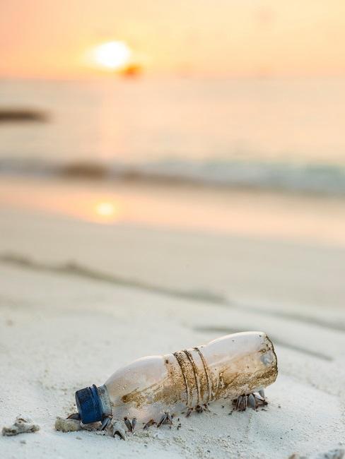 Schmutzige Plastikflasche im Sand am Strand