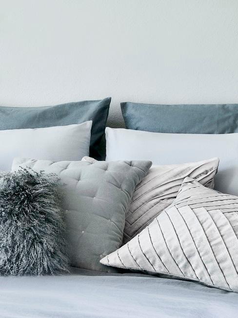 Bett vor einer grauen Wand mit vielen grauen Kissen