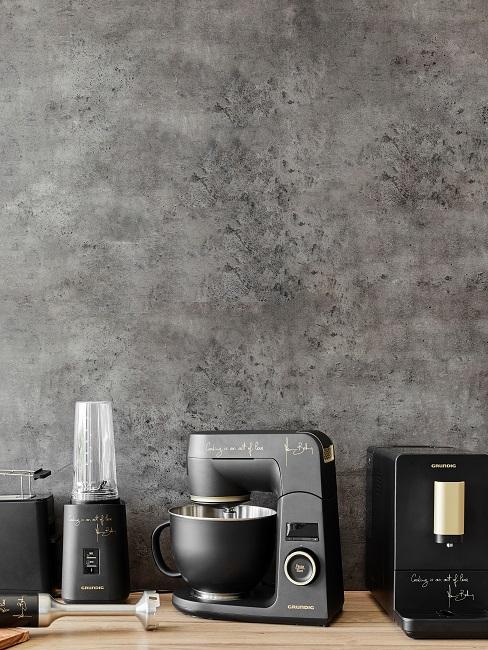 Schwarze Küchengeräte vor einer Betonwand