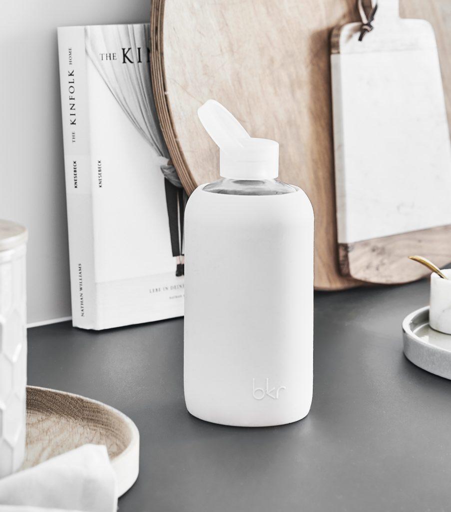 Weiße Trinkflasche vor Holzbrettern