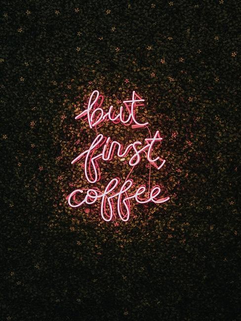 """Neon-Leuchtschrift in Rot an der Wand mit den Worten """"But first Coffee""""."""