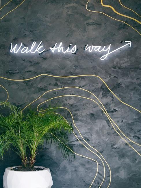 """Neon-Leuchtschrift """"Walk this Way"""" in Weiß an der Beton-Wand im Wohnraum."""