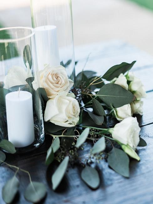 Tisch mit Kerzen in Windlichtern, daneben auf dem Tisch liegend ein Strauß heller Rosen
