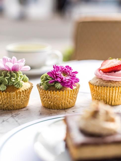 Tisch in Marmoroptik mit einem Kuchen, einer Tasse und drei Muffins, die mit Blüten dekoriert sind