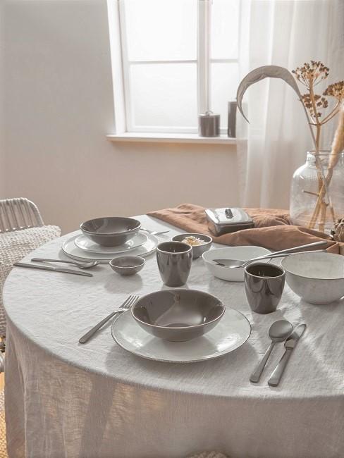 Hell gedeckter Tisch mit Leinentischdecke