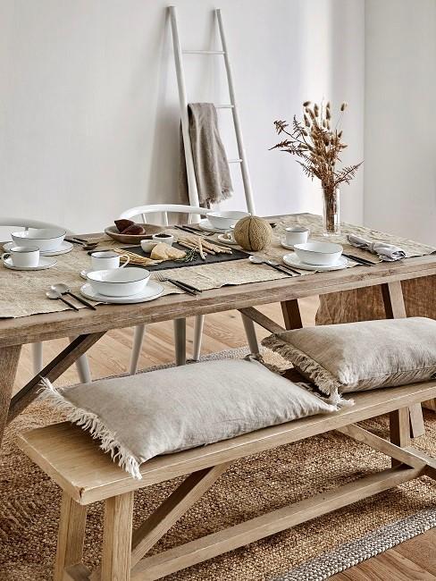 Esszimmr skandinavisch mit Holztisch, Holzbank und beigen Kissen