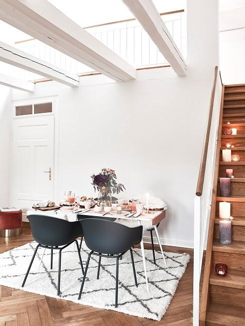 Esszimmer skandinavisch mit schwarzen Stühlen und gemustertem Teppich neben Treppe