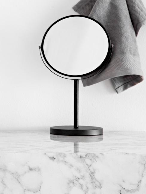 Kleiner Spiegel auf einer Marmor-Ablage.