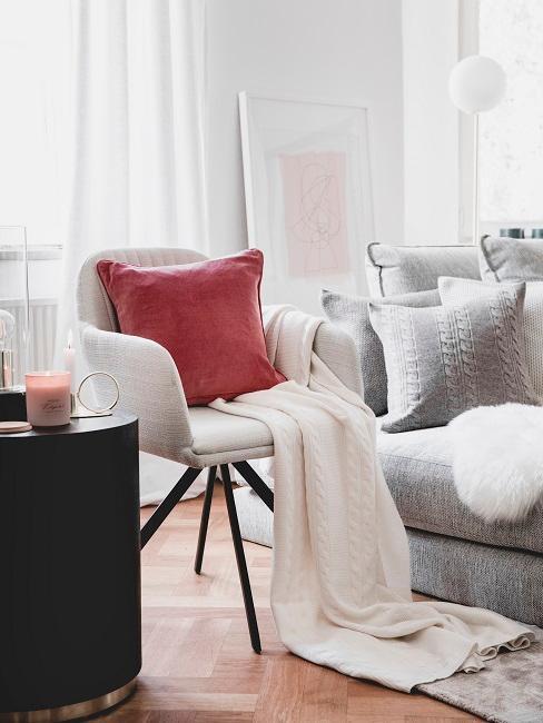 Rotes Kissen auf Ecru Sessel mit Ecru Decke