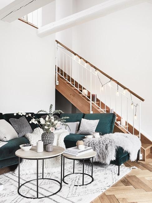 Treppenhaus gestalten mit Lichterkette neben grünem Sofa und Couchtisch