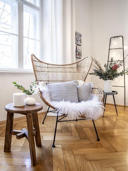 Schlafzimmer skandinavisch Sessel mit Fell und grauen Kissen und dunkler Holzhocker