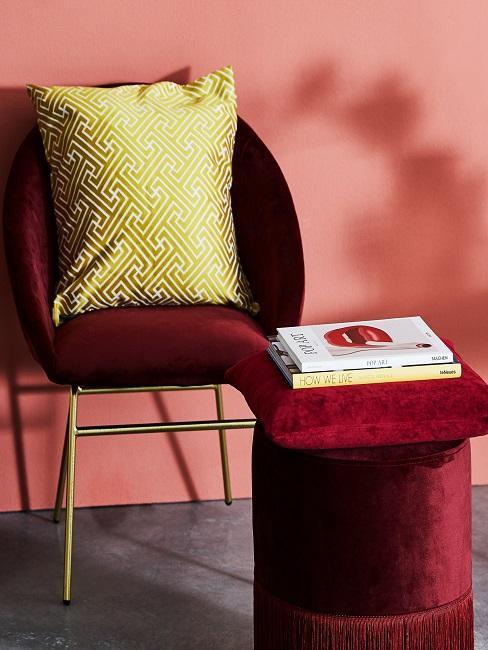 Roter Samtstuhl mit gelbem Kissen neben Pouf
