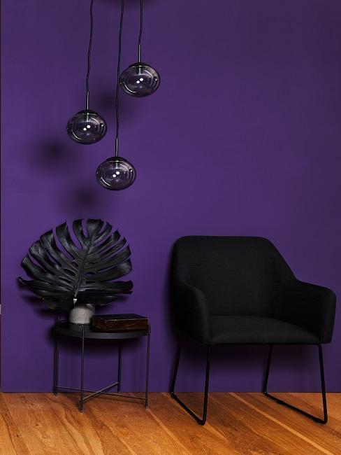 Schwarzer Stuhl und schwarze Dekoelemente vor lila Wand