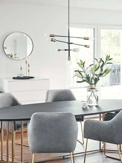 Der ovale Esstisch von Team Harrison mit Stühlen aus grauem Samt und einer Vase als Deko, darüber eine große Lampe