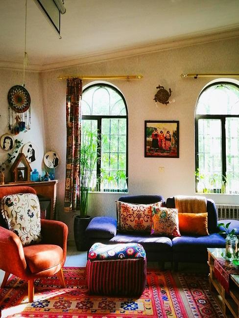 Raum mit bunt gemustertem Teppich und Kissen, einem Sofa in Blau zu einem braunen Sessel und einem Muster-Pouf, dazu Wandbehängung im indischen Ethno Stil