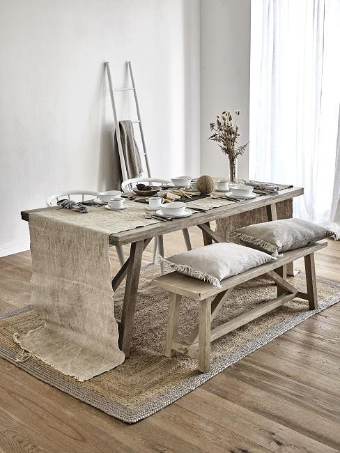 Kleines Esszimmer einrichten mit Holzbänken, Holztisch, Tischläufer und Teppich aus Jute