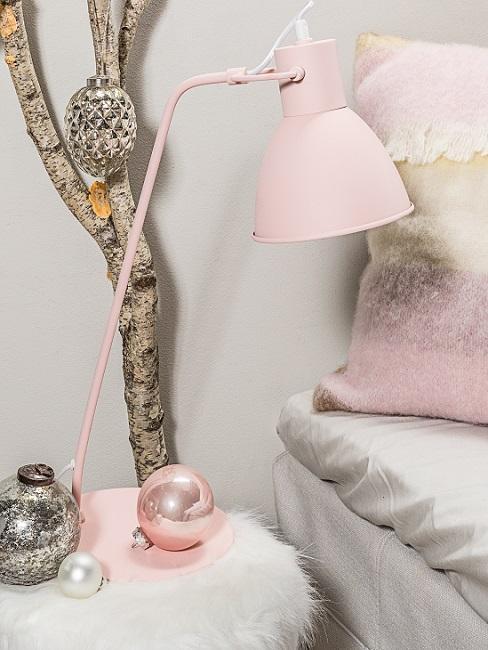 Ast dekorieren neben Nachttisch mit rosa Tischlampe und Weihnachtskugeln